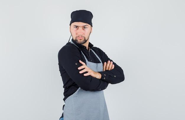 Mannelijke kok die zich met gekruiste armen in overhemd, schort bevindt en ernstig kijkt. vooraanzicht.