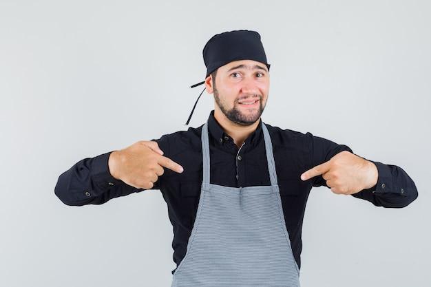 Mannelijke kok in overhemd, schort die naar zichzelf richt en beschaamd kijkt, vooraanzicht.