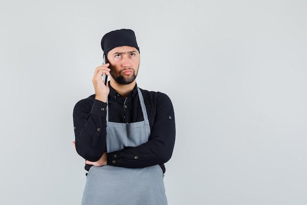 Mannelijke kok in overhemd, schort die op mobiele telefoon spreekt en ernstig, vooraanzicht kijkt.
