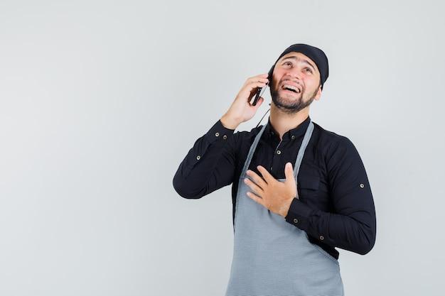 Mannelijke kok in overhemd, schort die op mobiele telefoon spreekt en vrolijk, vooraanzicht kijkt.