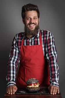 Mannelijke kok in rode schort die zich dichtbij verse zelfgemaakte zwarte hamburger bevindt en glimlacht