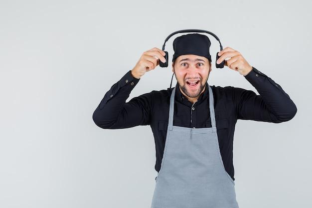 Mannelijke kok koptelefoon in shirt, schort dragen en op zoek vrolijk. vooraanzicht.
