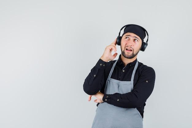 Mannelijke kok opzoeken met koptelefoon in shirt, schort vooraanzicht.