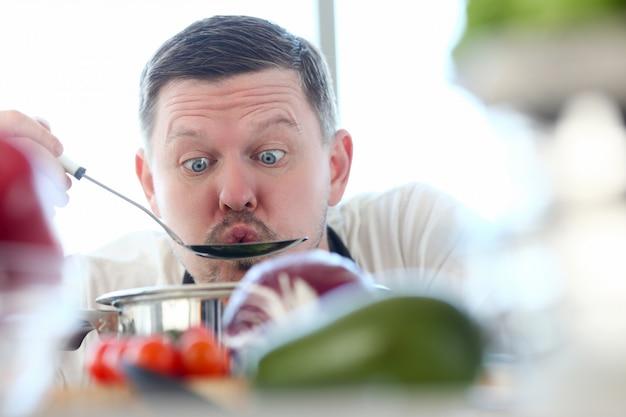 Mannelijke kok probeert hete soep uit de pan