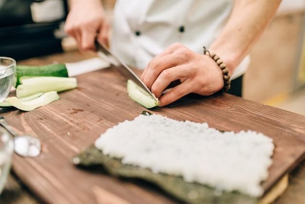 Mannelijke kok sushi rolt op de keuken maken