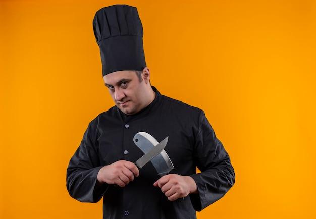 Mannelijke kok van middelbare leeftijd in chef-kok uniform kruising hakmes en mes op gele muur met kopie ruimte Gratis Foto