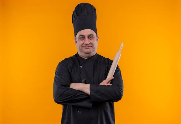 Mannelijke kok van middelbare leeftijd in chef-kok uniforme bedrijf deegroller kruising handen op gele muur met kopie ruimte