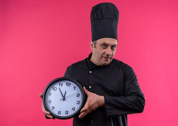 Mannelijke kok van middelbare leeftijd in de klok van de de holdingsmuur van de chef-kok eenvormige op geïsoleerde roze muur met exemplaarruimte