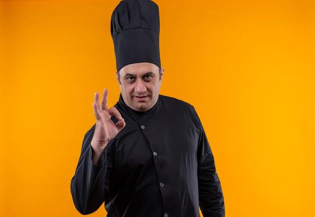 Mannelijke kok van middelbare leeftijd in eenvormige chef-kok die ok gebaar op gele muur toont