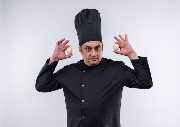 Mannelijke kok van middelbare leeftijd in uniform chef-kok met eieren rond het hoofd op geïsoleerde witte muur