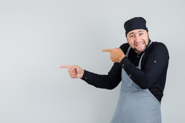 Mannelijke kok wijst naar de zijkant in overhemd, schort en ziet er vrolijk uit. vooraanzicht.