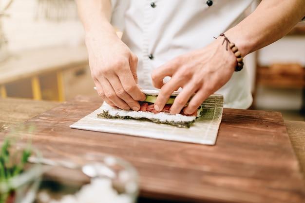 Mannelijke kok zeevruchten, aziatische keuken maken