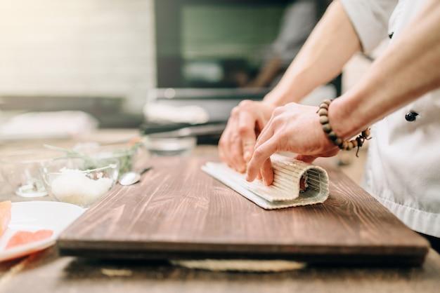 Mannelijke kok zeevruchten maken op houten tafel, aziatisch voedselbereidingsproces.