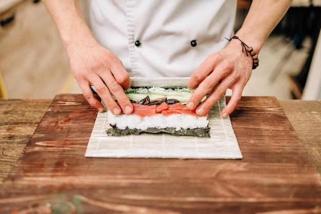 Mannelijke kok zeevruchten maken op houten tafel, aziatische keuken voorbereidingsproces.