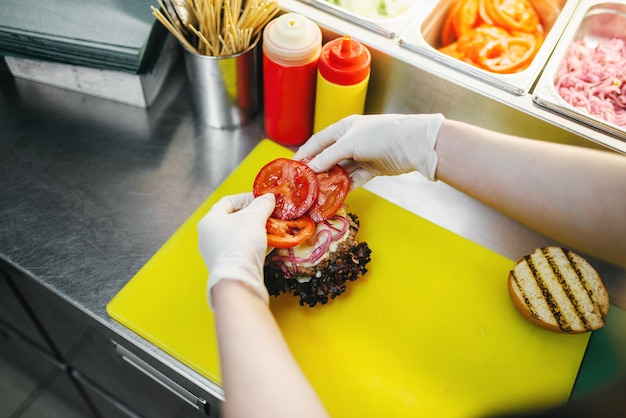 Mannelijke kok zet tomaten in de hamburger
