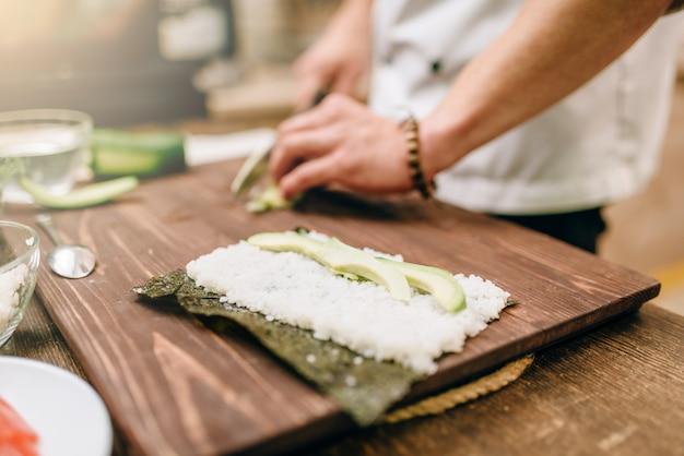 Mannelijke kokhanden die sushibroodjes, zeevruchten maken
