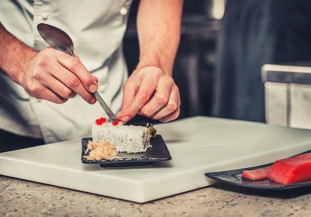 Mannelijke koks bereiden van sushi in de keuken van het restaurant