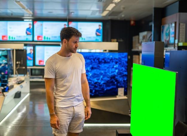 Mannelijke koper die televisie in de winkel kiest