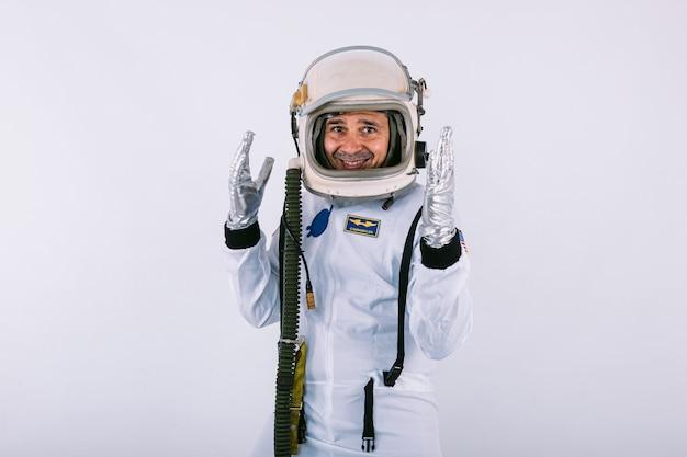 Mannelijke kosmonaut in ruimtepak en helm, die zijn handen met gebaar van pret, op witte achtergrond opheft.