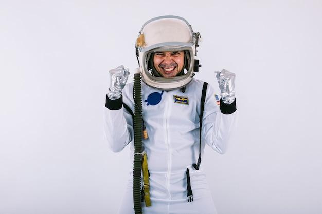 Mannelijke kosmonaut in ruimtepak en helm, handen omklemd in een teken van vreugde en kracht, op witte achtergrond.