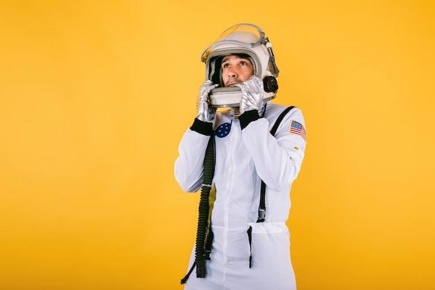 Mannelijke kosmonaut in ruimtepak en helm, helm met handen vasthoudend en naar links kijkend, op gele muur.