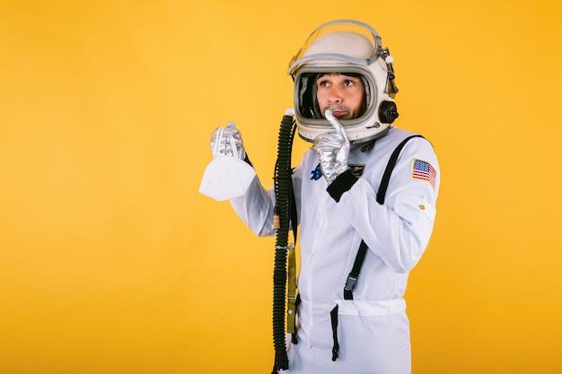 Mannelijke kosmonaut in ruimtepak en helm, met een fpp2-masker, op gele muur. covid19 en virusconcept