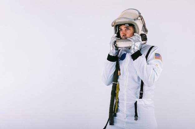 Mannelijke kosmonaut in ruimtepak en helm met helm met handen op witte achtergrond