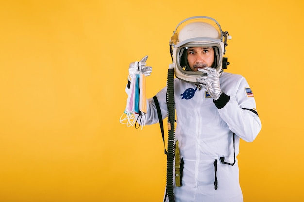 Mannelijke kosmonaut in ruimtepak en helm, met veel gekleurde chirurgische maskers, op gele muur. covid19 en virusconcept