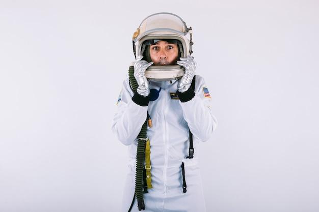 Mannelijke kosmonaut in ruimtepak en helm, met verbaasd gezicht dat de helm met zijn handen vasthoudt, op witte achtergrond.
