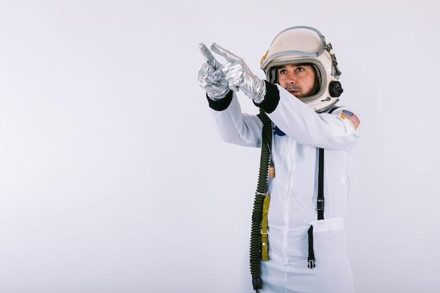 Mannelijke kosmonaut in ruimtepak en helm, wijzende vinger naar de hemel, op witte achtergrond.