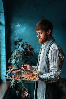 Mannelijke kunstenaar met palet en penseel in hand voor raam.