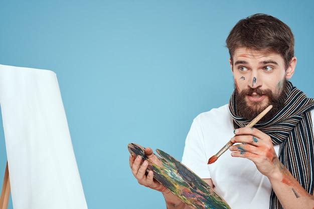 Mannelijke kunstenaar palet penseel ezel op een blauwe achtergrond