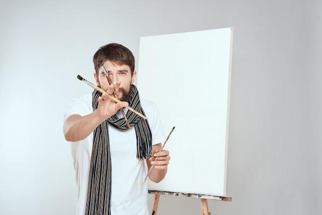 Mannelijke kunstenaar schildert een afbeelding op canvas met een ezel
