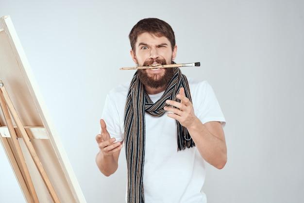 Mannelijke kunstenaar schildert een foto op canvas met een ezel