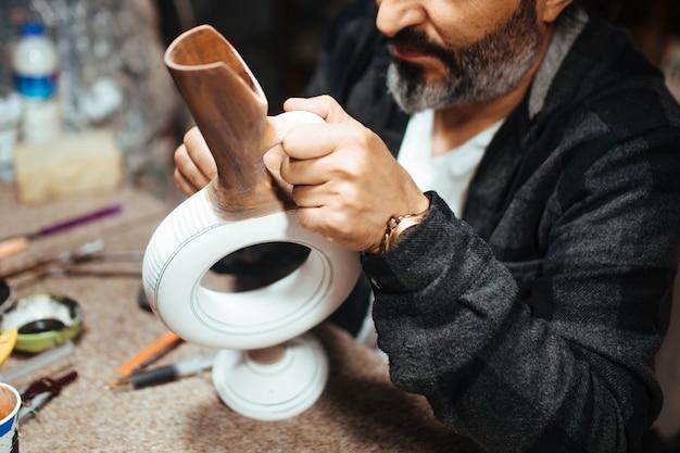 Mannelijke kunstenaar schildert een keramische vaas