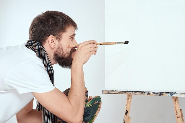 Mannelijke kunstenaar schildert op ezel