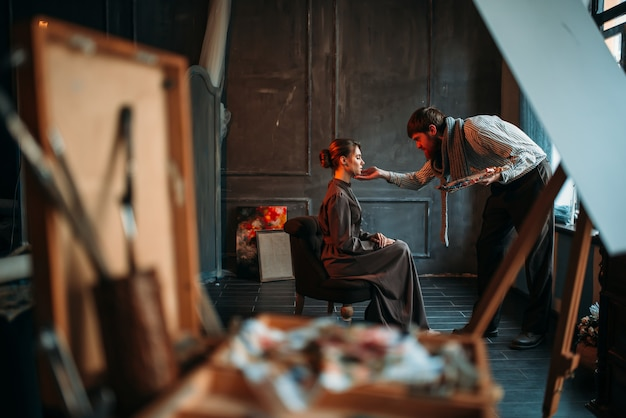 Mannelijke kunstenaar werkt met vrouwelijke poseur in art studio. olieverf, penseel tekening