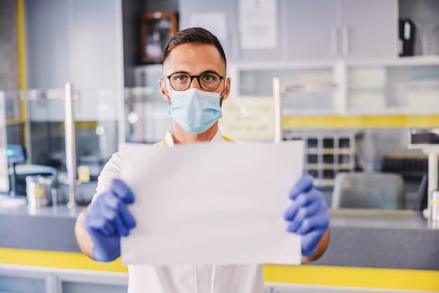 Mannelijke lab assistent permanent in hal van laboratorium en blanco papier te houden