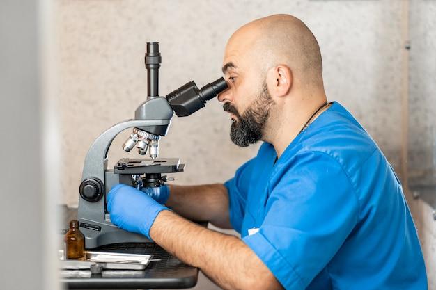 Mannelijke laboratoriummedewerker die biomateriaalsteekproeven in een microscoop onderzoekt