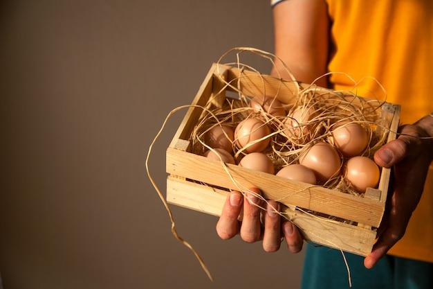 Mannelijke landbouwer die een houten doos met hooi en eieren daarin houdt