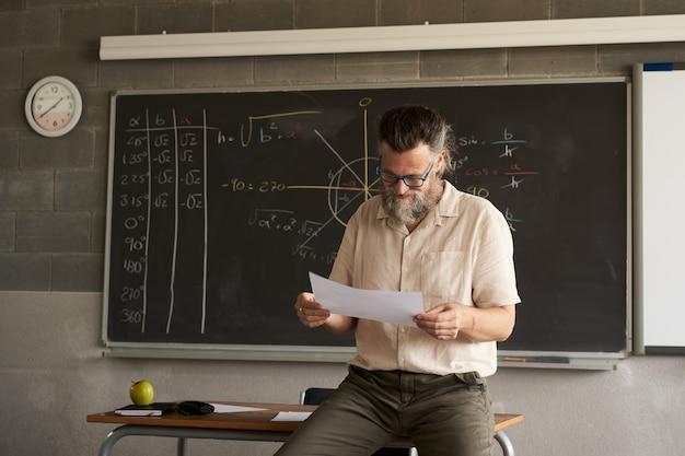 Mannelijke leraar bereidt examens voor of corrigeert ze in de klas