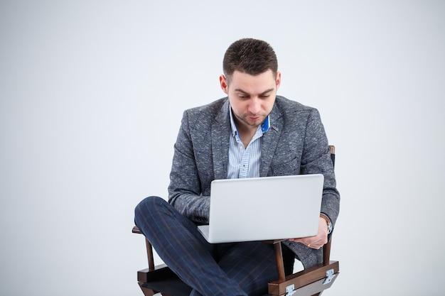 Mannelijke leraar directeur zakenman zittend op een stoel documenten bestuderen. hij kijkt naar het scherm van de laptop. nieuw zakelijk project.