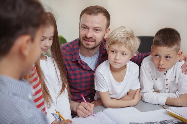 Mannelijke leraar werken met kinderen op de kleuterschool