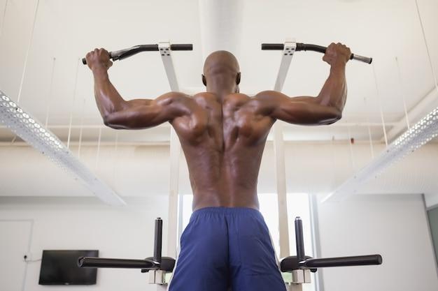 Mannelijke lichaamsbouwer die trekkracht ups doen bij de gymnastiek