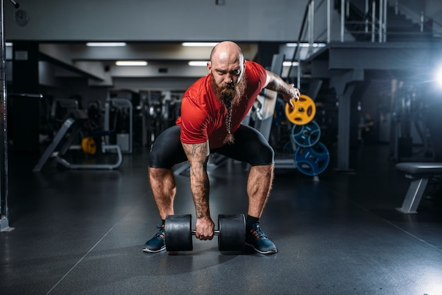 Mannelijke lifter doen oefening met halters in sportschool