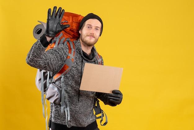 Mannelijke lifter met leren handschoenen en rugzak met lege kartonnen wuivende hand