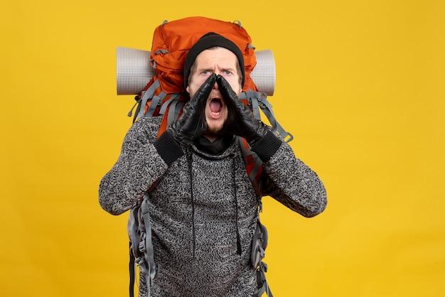 Mannelijke lifter met leren handschoenen en rugzak schreeuwen