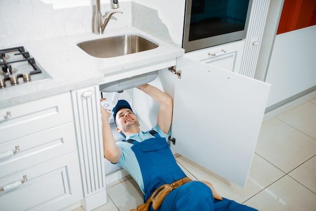Mannelijke loodgieter in uniform installeren afvoerpijp in de keuken. klusjesvrouw met gereedschapstas reparatie gootsteen, sanitair service aan huis