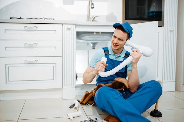 Mannelijke loodgieter in uniform luistert naar de afvoerpijp in de keuken, humor. klusjesvrouw met gereedschapstas reparatie gootsteen, sanitair service thuis