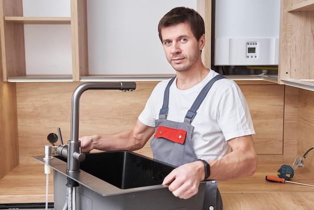 Mannelijke loodgieter installeert een gootsteen in de keuken